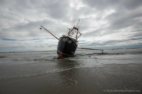 FAR ROCKAWAY, QUEENS, NEW YORK CITY, NY/USA – FEBRUARY 25, 2016: The 24 meter (78 foot) scallop fishing vessel the Carolina Queen III, rests in heavy surf in the Atlantic ocean off Far Rockaway on the Rockaway peninsula of the borough of Queens in New York City. The boat ran aground at about 2am and all the crew were safely evacuated by the US Coast Guard.